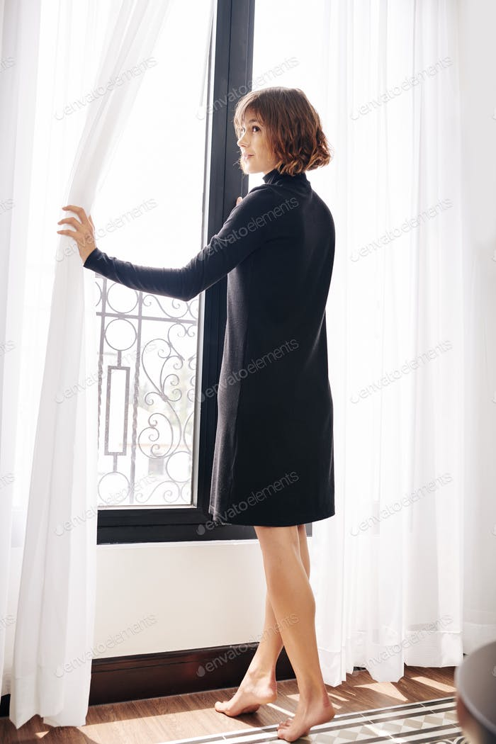 Young barefoot woman opening curtains
