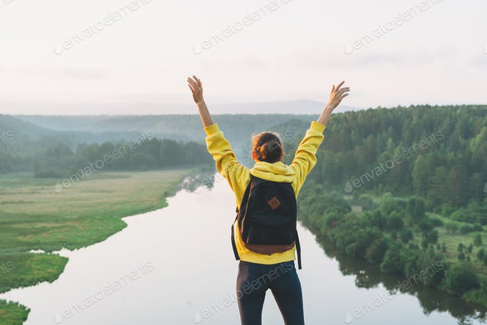 Young woman girl traveler in yellow hoodie with backpack looking on beautiful view
