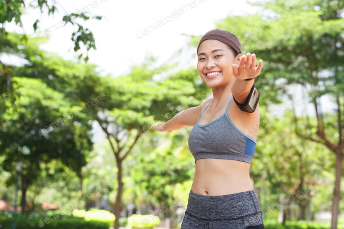 Cheerful sportswoman working out in park