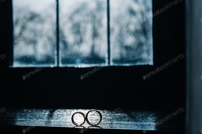 two gold wedding rings on the windowsill in the sunlight