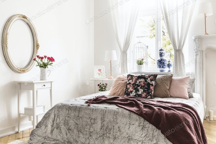 Sweet bedroom interior with a bed covered with a silver throw, a
