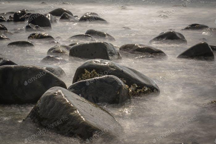 Felsige Steine in verschwommenem Wasser durch lange Belichtung