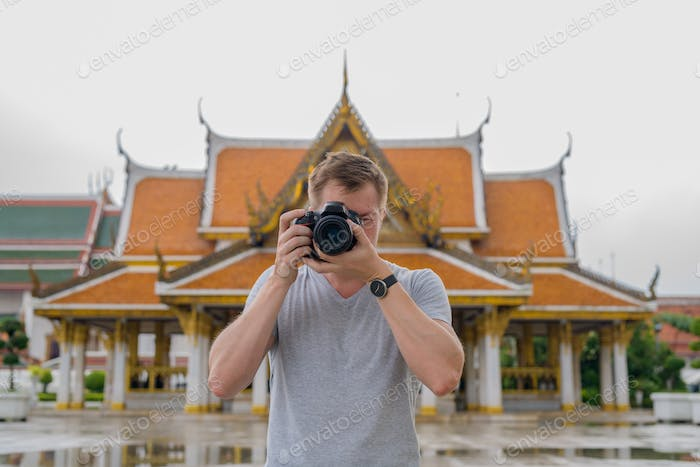 Young tourist man taking picture with camera against view of the Buddhist temple in Bangkok