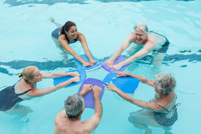 Senior swimmers with trainer enjoying in swimming pool