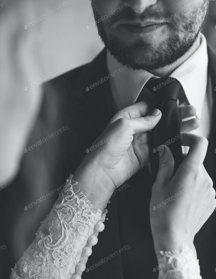 Bride Helping Groom Dressing Up for Wedding Ceremony
