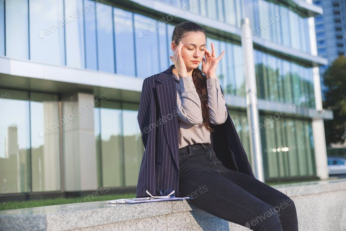 Young woman in suit settles herself down after stressful work.