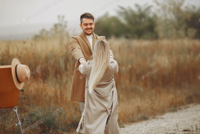 Beautiful couple spend time in a autumn field
