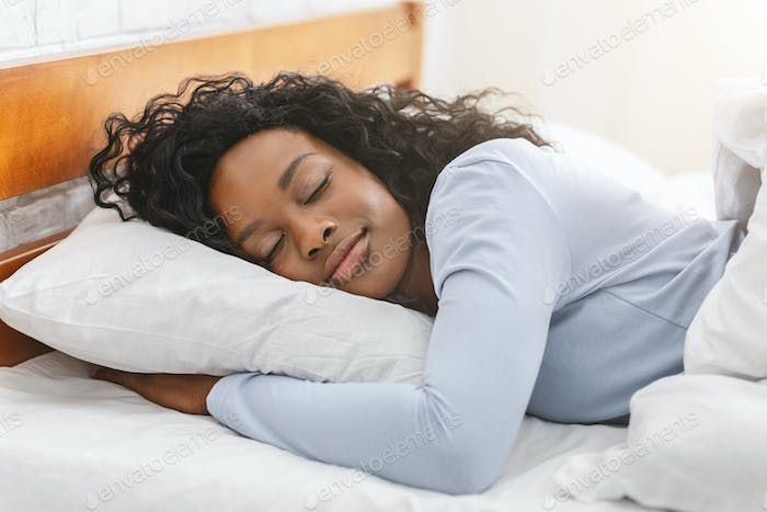 Peaceful afro girl sleeping in bed in morning