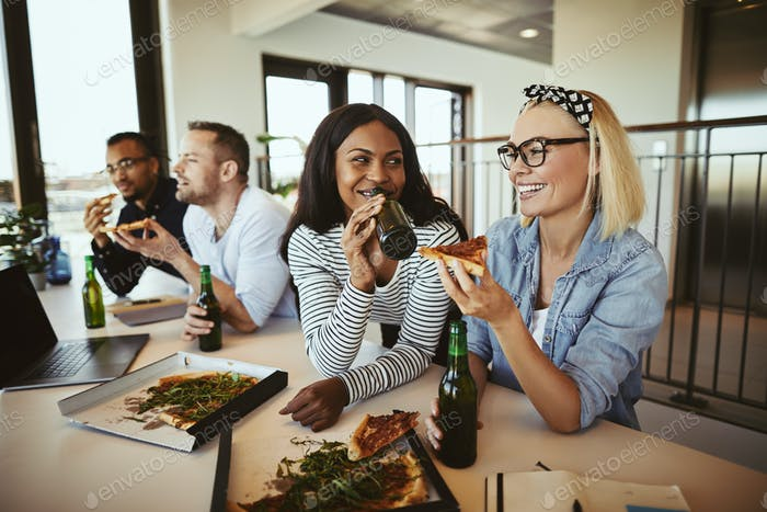 Two smiling businesswomen having pizza and beers after work