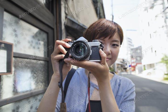 Frau steht draußen, schaut durch eine Kamera.
