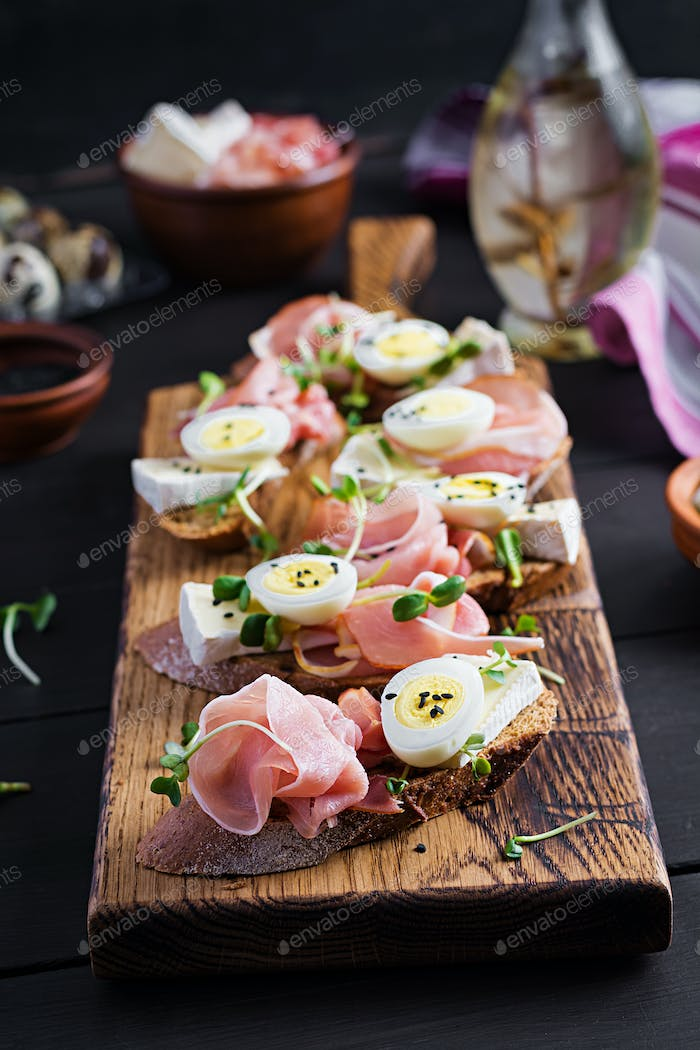 Delicious snack with bread, brie cheese and quails eggs.