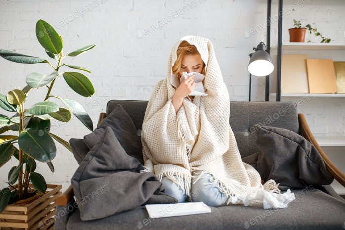 Sick woman sitting with kerchief under the blanket