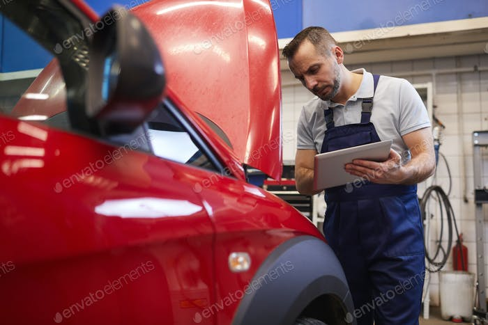 Mechanic Inspecting Car in Workshop