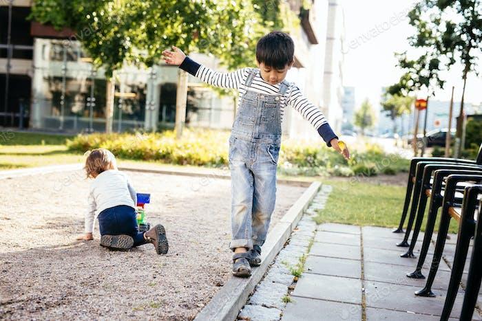 Boys (2-3, 4-5) playing at playground