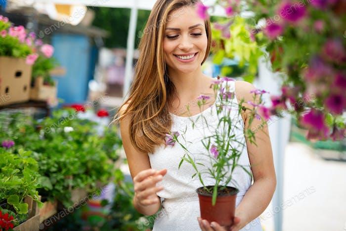Portrait of young female shopper walking through indoor garden store