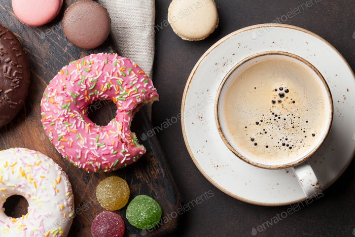 Coffee cup and colorful donuts