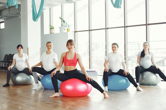 Pregnant women doing yoga with a coach