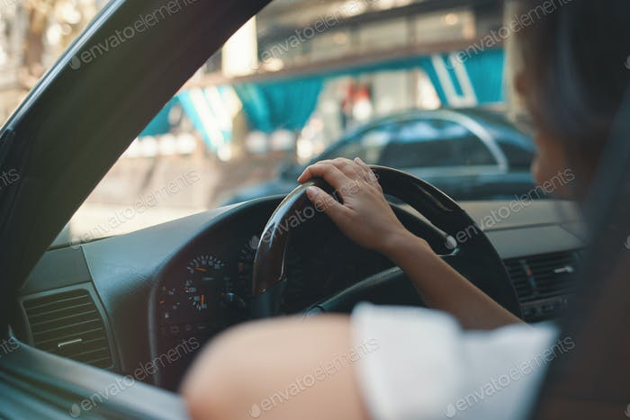 Close-up woman holding hand on steering wheel