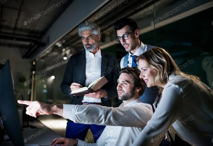 A group of business people in an office at night, using computer.
