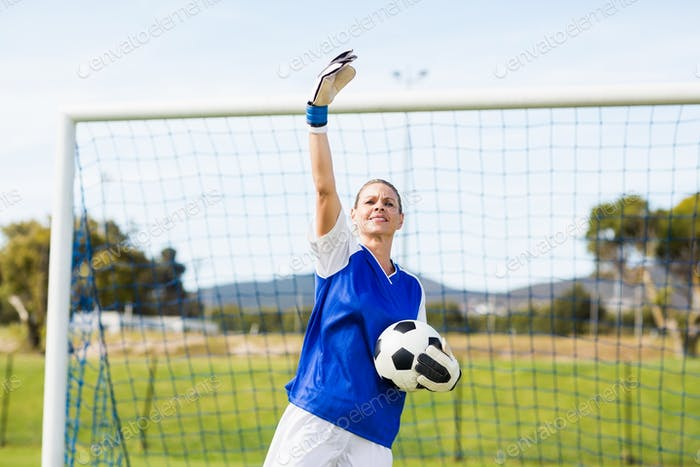 Female goalkeeper holding a ball and gesturing