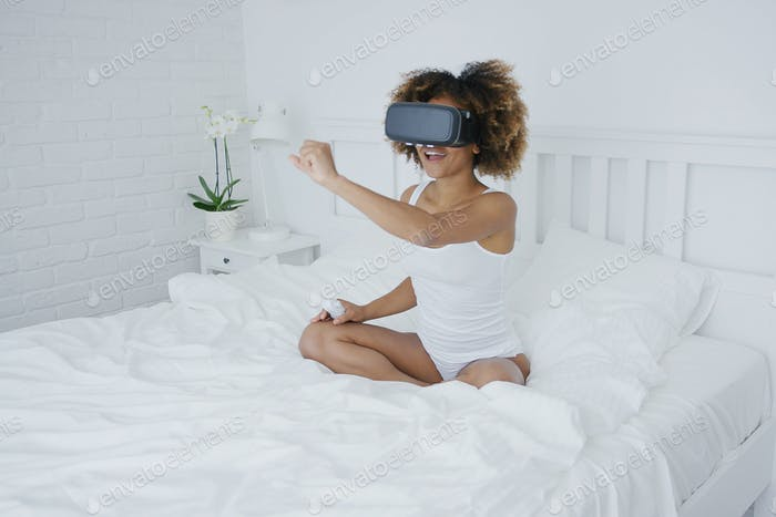 Content woman in VR glasses on bed