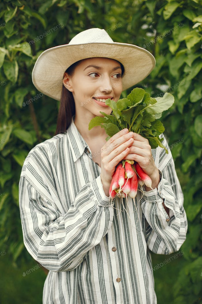 Woman in a hat holding fresh radishes