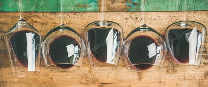 Red wine in glasses over rustic wooden background, wide composition