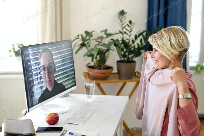 Woman having video call on computer at home, friend giving fashion advice