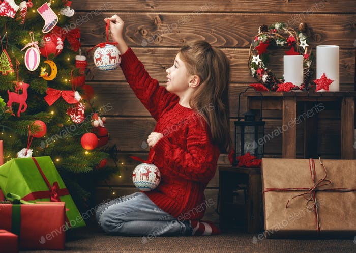 Mädchen schmückt den Weihnachtsbaum