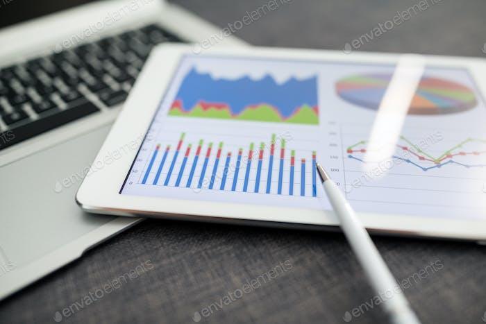 Arbeitsplatz mit Tablet-PC zeigt Diagramme