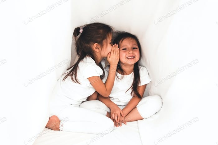 Cute little girl whispering something to her sister under the cover
