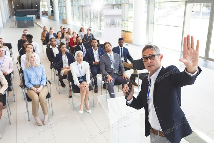 Male speaker speaks with microphone to diverse business people in a business seminar in office