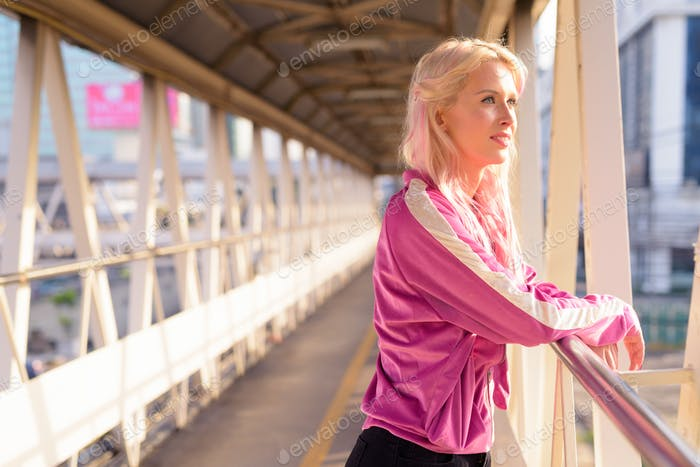Happy young beautiful blonde woman thinking at footbridge in the city