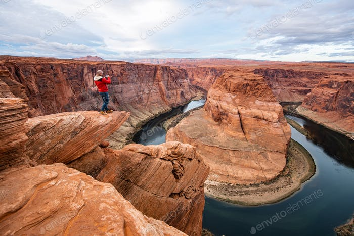 Man sitting on a cliff over Colorado river in Horseshoe bend canyon