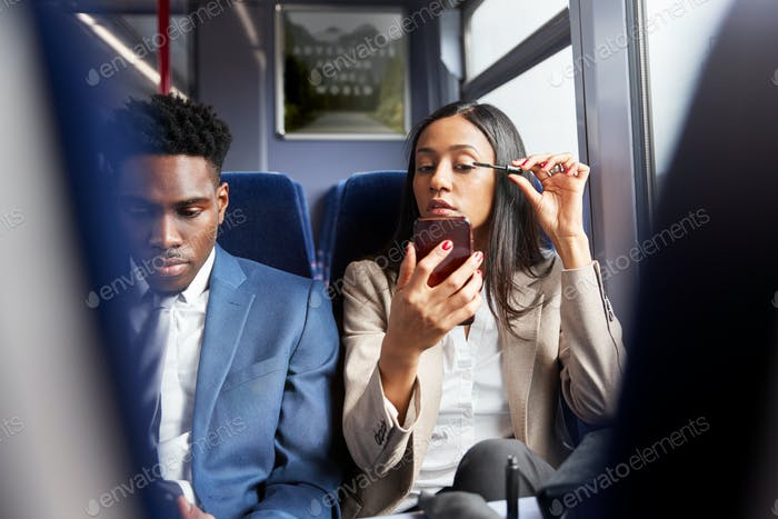 Businesswoman Sitting In Train Commuting To Work Putting On Make Up