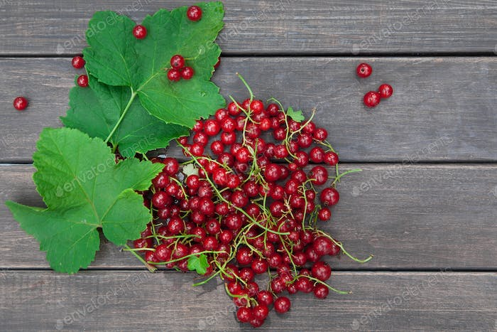 Red currants heap closeup on rustic wood background