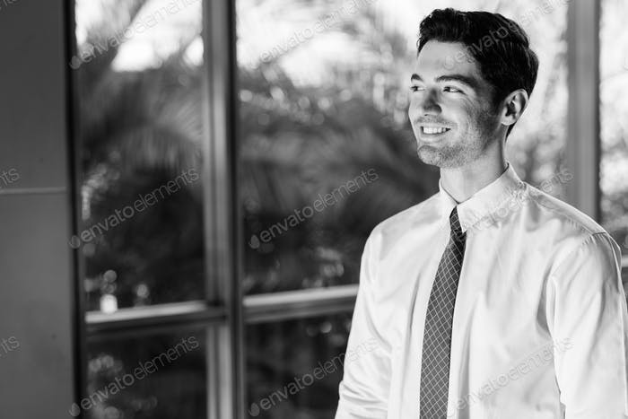 Portrait of happy young handsome businessman by the glass window