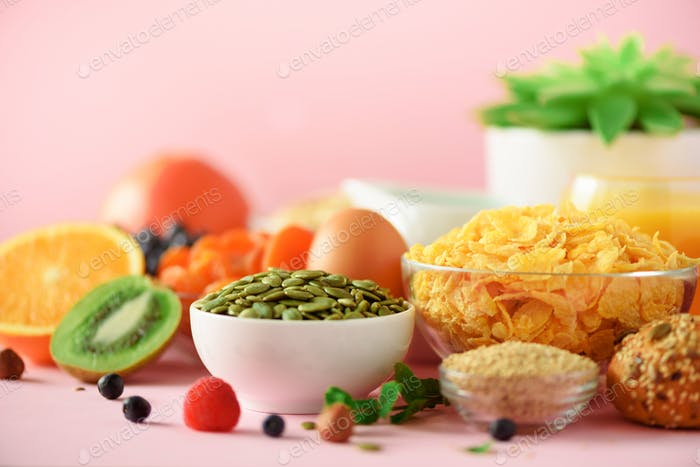 Cornflocken mit Milch, Kürbiskerne, frische Beeren, Joghurt, gekochtes Ei, Nüsse, Früchte, Orange