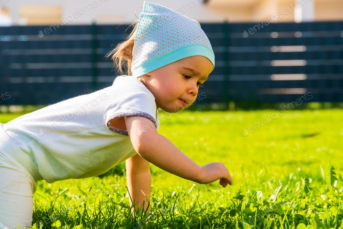 Cute baby on all fours in red body on green grass in summer day.