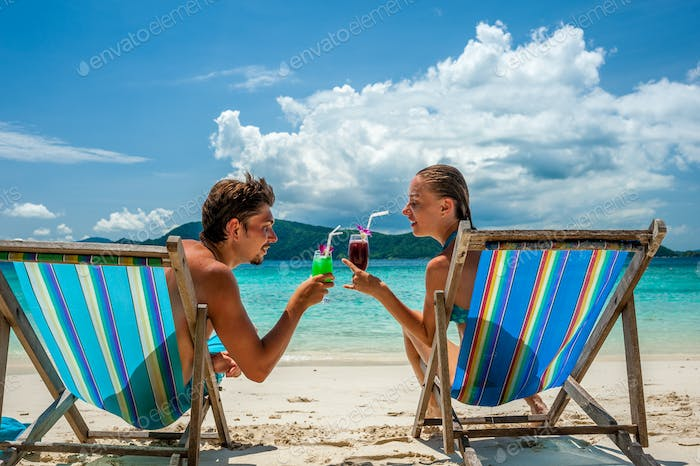 Couple in loungers on a beach at Thailand