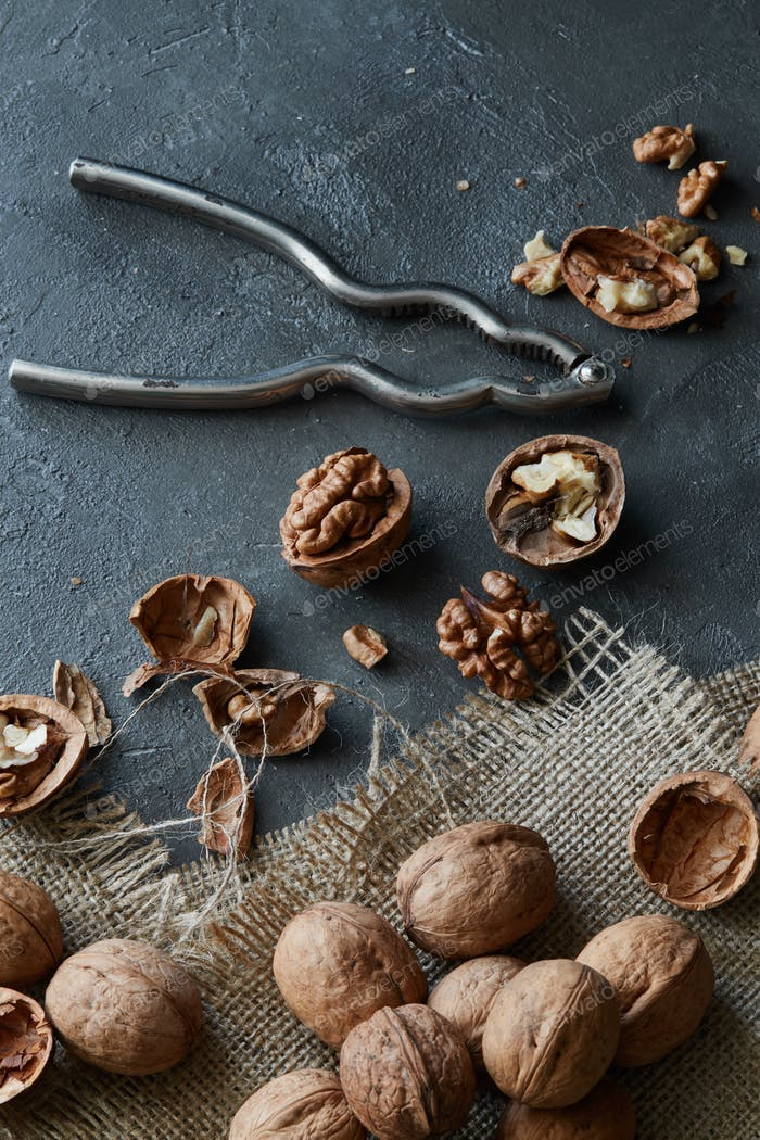 Walnuts and kernels with burlap fabric on a grey concrete backdrop with vintage nutcracker