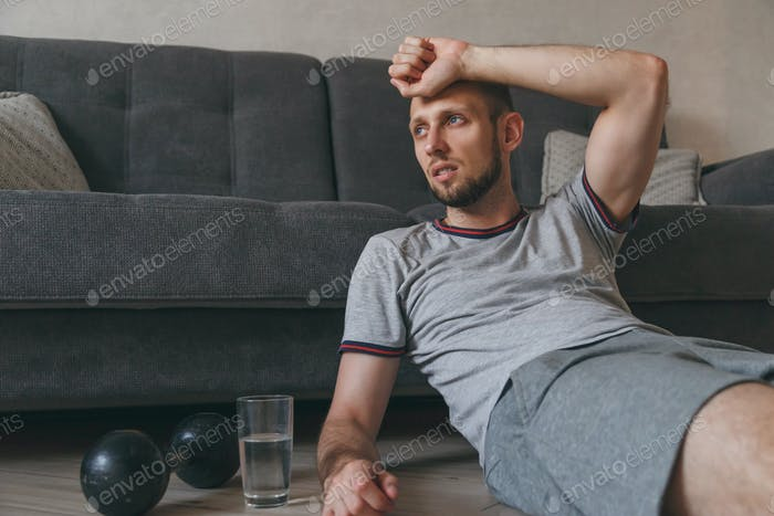 Exhausted man sitting on floor breathing and resting after heavy cardio training at home