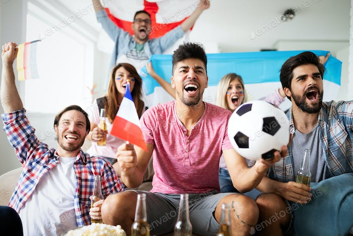 Soccer fans emotionally watching game in the living room
