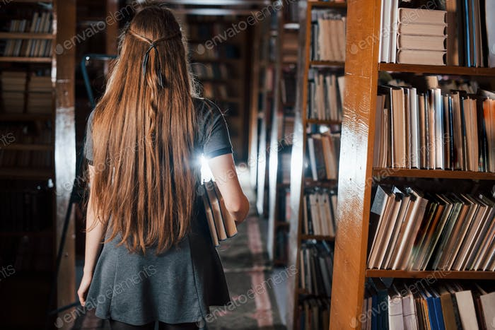 Back view. Female student is in library that full of books. Conception of education