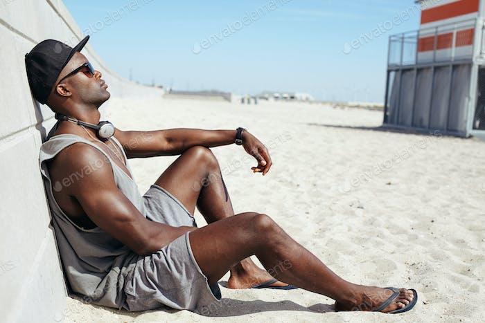 Mann sitzt am Strand entspannend
