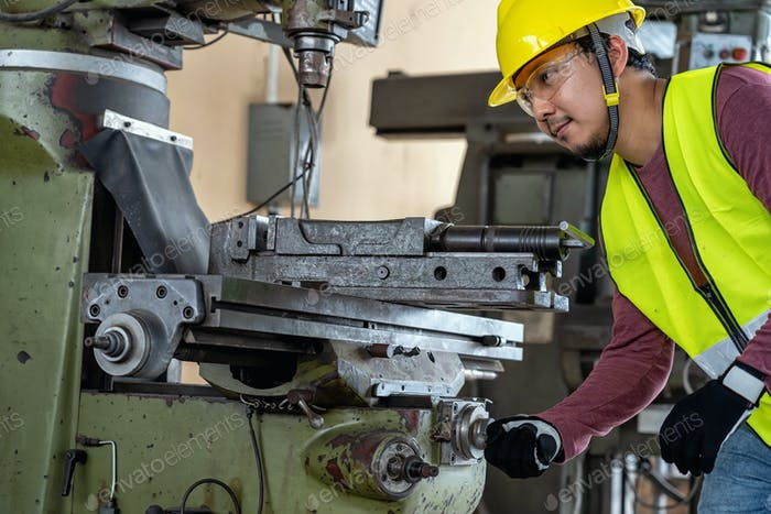 Asian machinist in safety suit operating the professional lathes in metalworking factory,