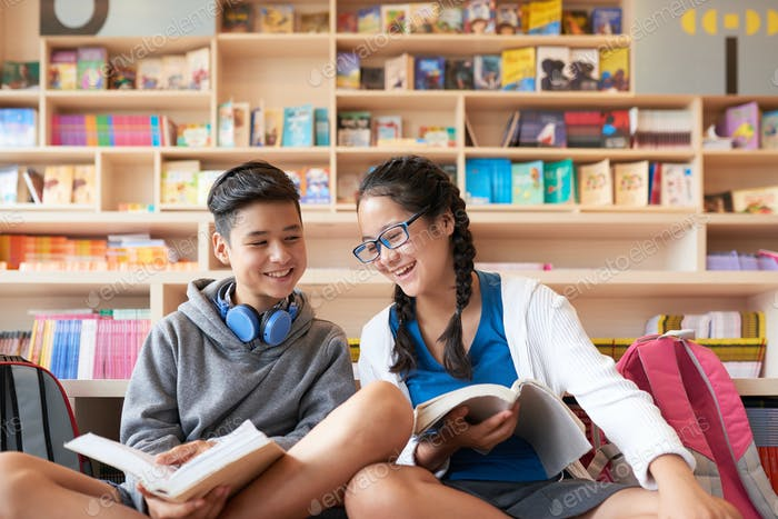 Teenagers sitting in library with books smiling