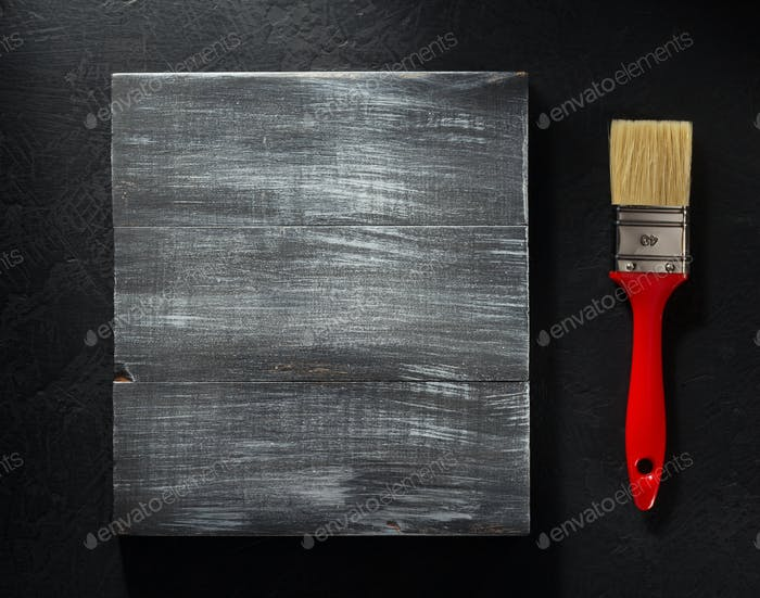 paintbrush and board on black