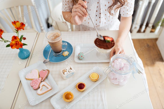 Young woman eating dessert and drinking latte at the table