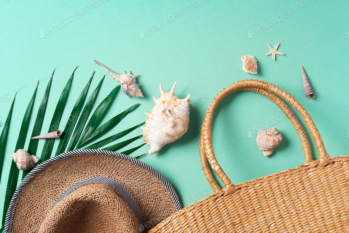 Summer fashion flat lay. Stylish straw bag, hat, palm leaves, shells on trendy green background. Top